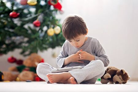 android tablet: Cute little boy and his monkey toy, playing on tablet in front of a christmas tree