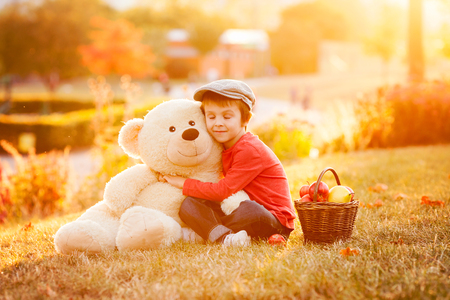 cute teddy bear: Adorable little boy with his teddy bear friend in the park on sunset, nice back light