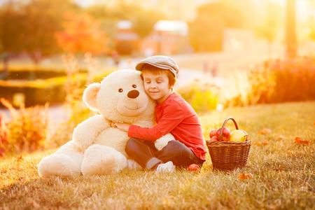 teddy bear: Adorable ni�o con su amigo el oso de peluche en el parque en la puesta del sol, luz de fondo agradable Foto de archivo