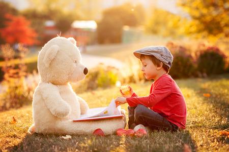 Schattige kleine jongen met zijn teddy beer vriend in het park op zonsondergang, mooi weer licht Stockfoto