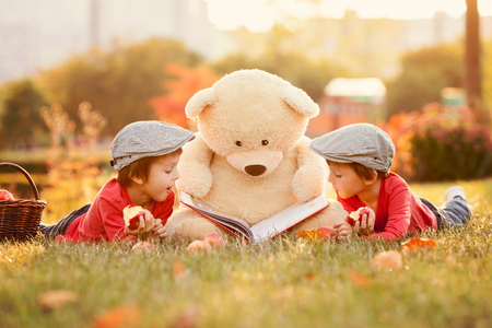 Two adorable little boys with teddy bear friend in the park on sunset, nice back light
