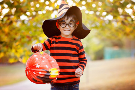 background yellow: Cute boy in the park with halloween costume, hat and glasses, having fun autumn time
