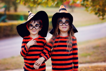 Boy and girl in the park in halloween costumes, having fun autumn time