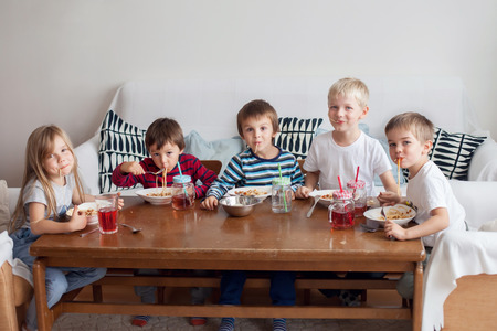 dining room: Five adorable kids, eating spaghetti at home, having fun Stock Photo