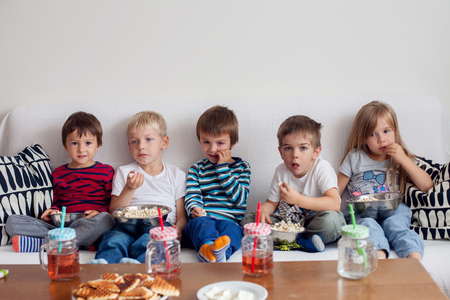 Five sweet kids, friends, sitting in living room at home, watching TV and eating popcorn Stock Photo