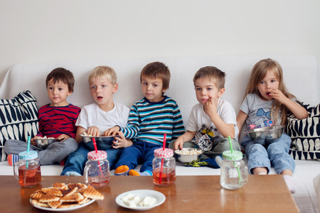 Five sweet kids, friends, sitting in living room at home, watching TV and eating popcorn Standard-Bild