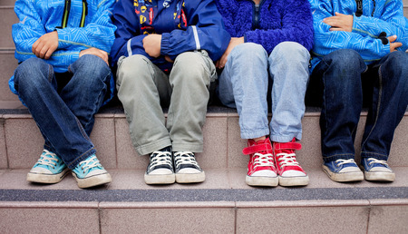 red jeans: Sneakers on a kids feet, sitting on a stairs Stock Photo