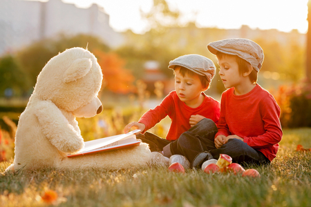 Due ragazzini adorabili con orsacchiotto amico nel parco al tramonto, bella luce indietro Archivio Fotografico - 46413619