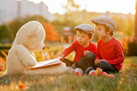Twee schattige kleine jongens met teddy beer vriend in het park op zonsondergang, mooi licht terug