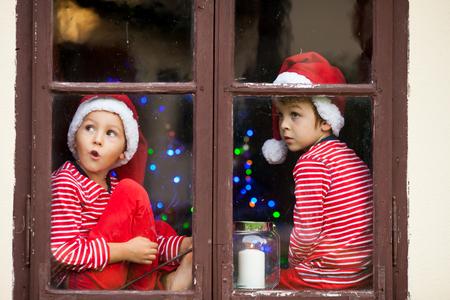 Twee leuke jongens, broers, kijkend door een raam, ongeduldig wachtend op de kerstman