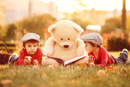 oso de peluche: Dos niños adorables con amigo oso de peluche en el parque en la puesta del sol, luz de fondo agradable Foto de archivo