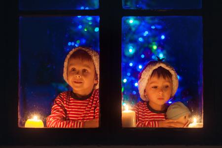 Twee lieve jongens, zittend op een raam, op zoek naar buiten, wintertijd, wachten ongeduldig voor de kerst te komen Stockfoto