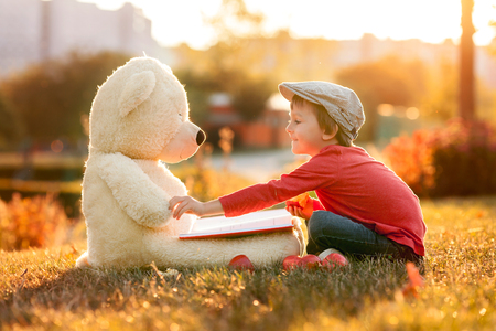 fall foliage: Adorable little boy with his teddy bear friend in the park on sunset, nice back light