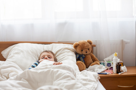 child: Sick child boy lying in bed with a fever, resting at home