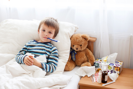 Sick child boy lying in bed with a fever, resting at home