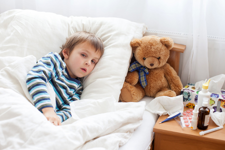 sick teddy bear: Sick child boy lying in bed with a fever, resting at home