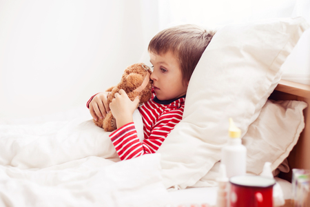 the sick: Sick child boy lying in bed with a fever, holding terry bear with band aid, resting