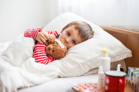 niños enfermos: Sick boy niño acostado en la cama con fiebre, la celebración de oso de felpa con la ayuda de venda, descansando