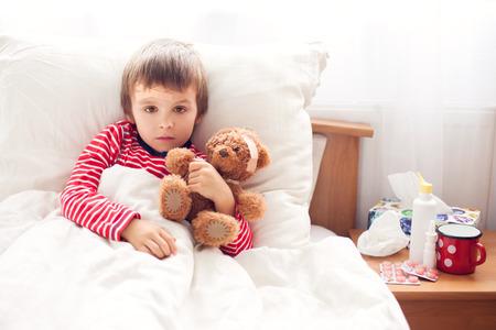 Ziek kind jongen liggend in bed met koorts, met badstof beer met pleister, rusten Stockfoto