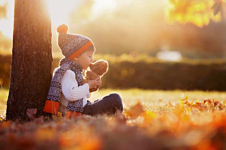 Schattige kleine jongen met teddybeer in het park op een herfst dag in de middag, zittend op het gras
