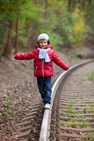 hand rails: Cute boy walking on a railroad, smiling, autumn time