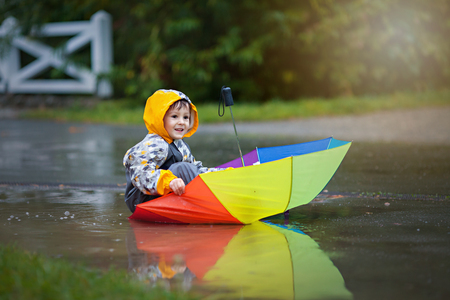 Cute boy with colorful rainbow umbrella on a rainy day, having fun playing in the park in muddy puddles Archivio Fotografico