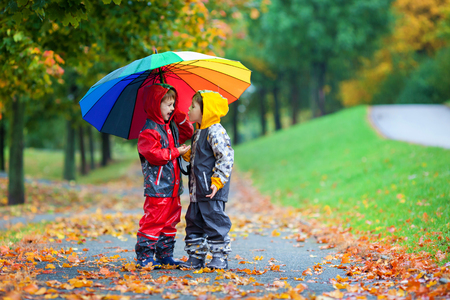 Two adorable children, boy brothers, playing in park with colorful rainbow umbrella on a rainy autumn day