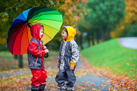 weather: Two adorable children, boy brothers, playing in park with colorful rainbow umbrella on a rainy autumn day