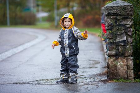 botas de lluvia: Muchacho lindo en el parque, jugando bajo la lluvia, saltando en los charcos, las salpicaduras de agua Foto de archivo