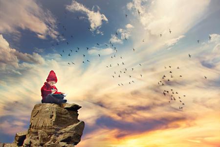 escritura: Chico, sentado en una roca en el cielo, los pájaros que vuelan alrededor de él, escribiendo carta a los Reyes Foto de archivo