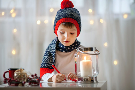 letter writing: Adorable little child, boy, writing letter to Santa