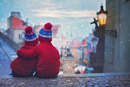 Two cute kids, boys, standing on stairs, holding a lantern, view of Prague behind them, snowy evening