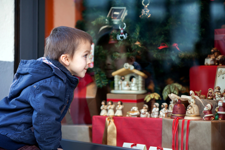 show window: Sweet little boy, looking through a window in shop, decorated for Christmas holidays