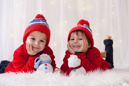 fiesta familiar: Sweet children, brother boys, playing with handmade snowmen at home, christmas lights behind them
