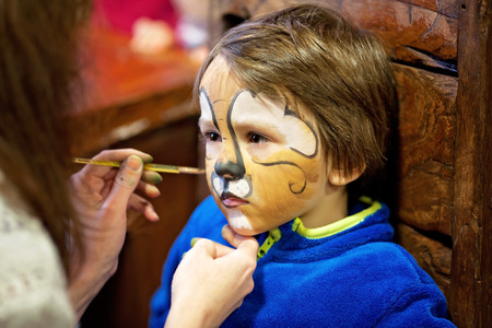 painted face: Little boy with painted face as a lion for a carnival Stock Photo