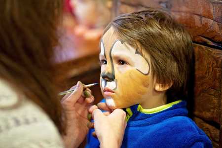 hair mask: Little boy with painted face as a lion for a carnival Stock Photo
