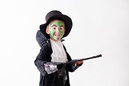 mago: Muchacho lindo con la cara pintada como aa mago y vestido con traje mago, divertirse, tiro del estudio