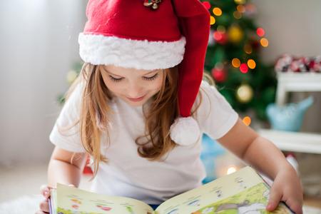 jolie petite fille: Belle fille, la lecture d'un livre en face de l'arbre de No�l, d�tail tir� sur les cils