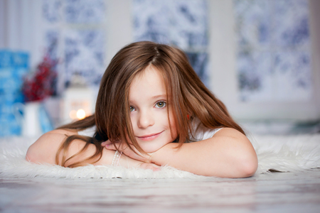 little girl smiling: Beautiful winter close portrait of little preschool girl at home, dreaming