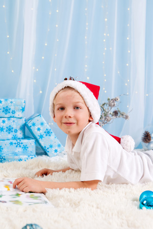 beautiful boy: Sweet boy, reading a book on Christmas, decoration around him, studio shot