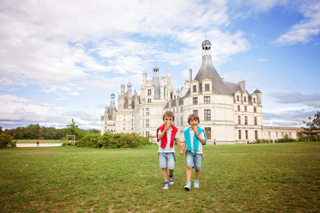 arousing: Two adorable boys in casual clothing, eating ice cream sitting on a lawn in front of the biggest castle along the Loire river, Chambord, on sunset, castle magnificiently arousing behind them