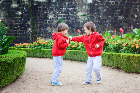 sibling rivalry: Two kids, boy brothers, fighting in garden, summertime rainy day Stock Photo