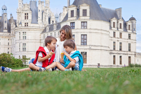Two adorable boys and mom in casual clothing, eating ice cream sitting on a lawn in front of the biggest castle along the Loire river, Chambord, on sunset, castle magnificiently arousing behind them