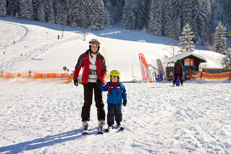 kids at the ski lift: Beautiful young mom and her toddler boy, skiing in the mountains, winter time Stock Photo
