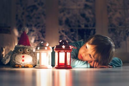 Mooie kleine jongen, liggend op de grond, op zoek naar kaarsen, het maken van wensen voor Kerstmis Stockfoto