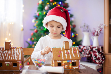 home decorating: Cute little boy, making gingerbread cookies house, decorating at home in front of the Christmas tree, child playing and enjoying, Christmas concept
