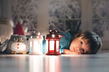Niño pequeño hermoso, acostado en el piso, mirando las velas, por lo que los deseos para la Navidad Foto de archivo - 49968341