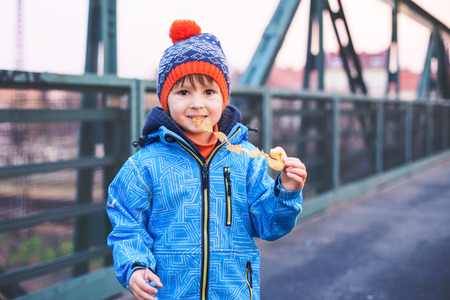 eating fast food: Cute boy, eating potato chips on a bridge, outdoors, wintertime Stock Photo