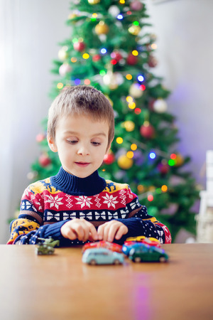 chrstmas: Adorable little preschool boy, playing with toy cars at home on Christmas, Christmas decoration around him