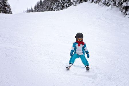 cool down: Adorable little boy with blue jacket and a helmet, skiing wintertime Stock Photo